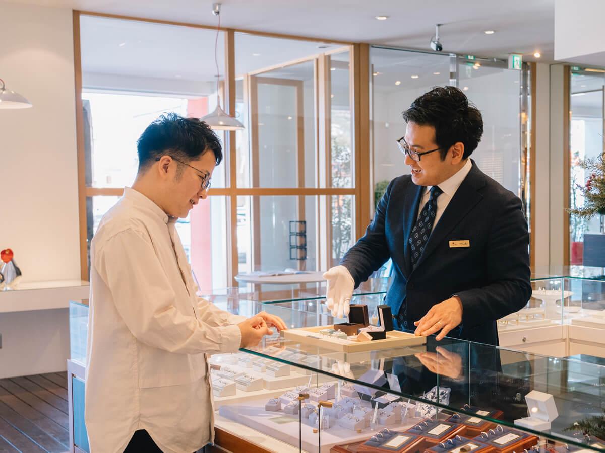 丁寧に案内する販売員と効率的に婚約指輪を検討中の男性