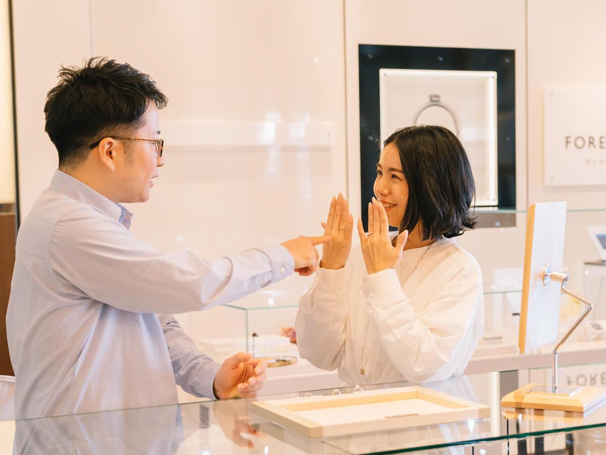 カップルがふたりで一緒に楽しく婚約指輪を選んでいます