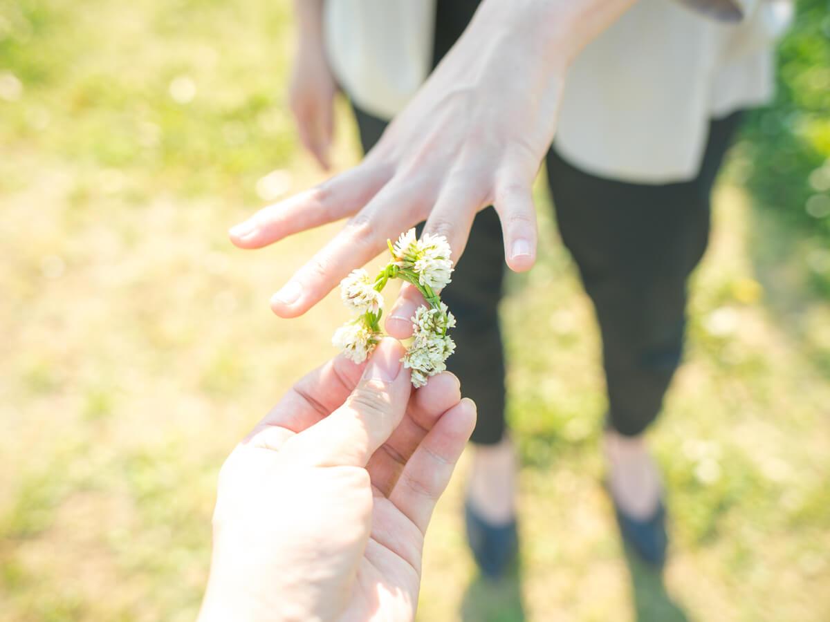 左手の薬指に花で作った指輪を彼女に着けてあげる男性